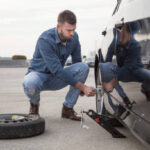 Young man changing a flat tire on his car. About 30 years old, Caucasian male.;